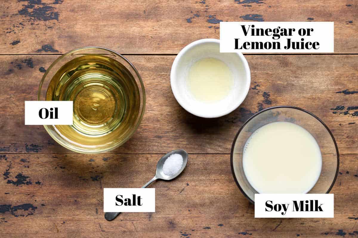 Table with ingredients for vegan mayo: oil, vinegar, soy milk, salt.