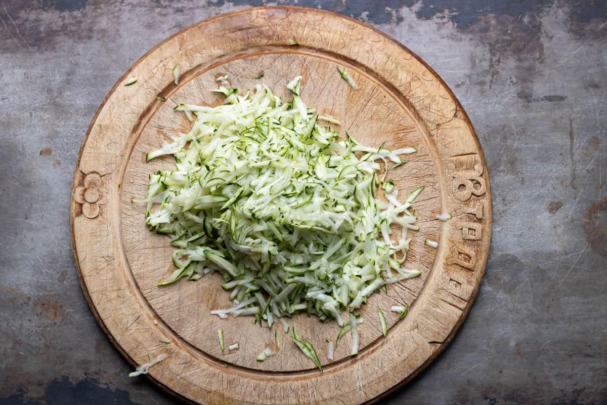 Shredded zucchini on a wooden cutting board.