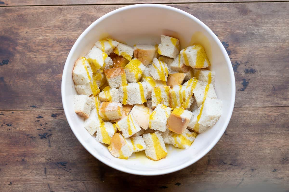Bread cubes in a bowl drizzled with oil and seasonings.