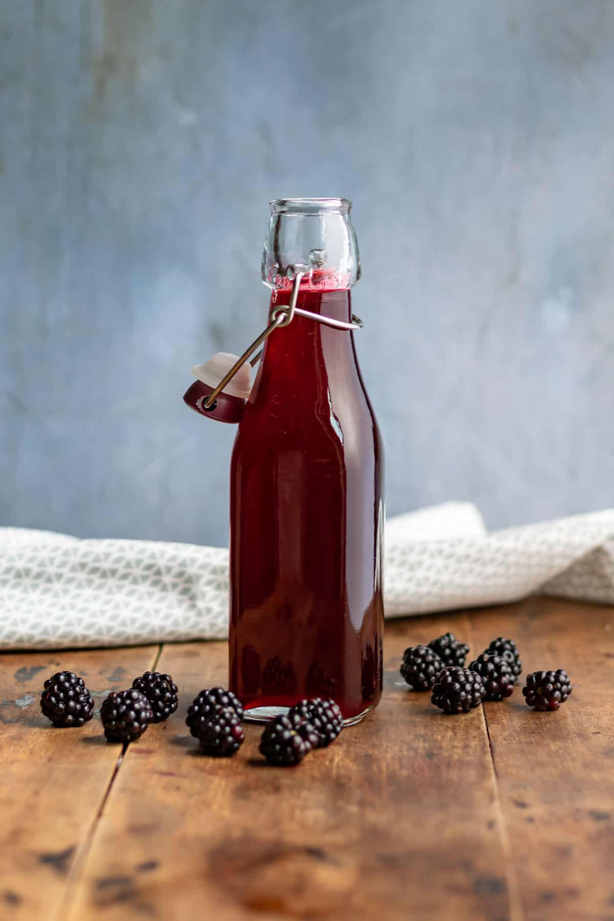 Bottle of blackberry syrup on a wooden table.