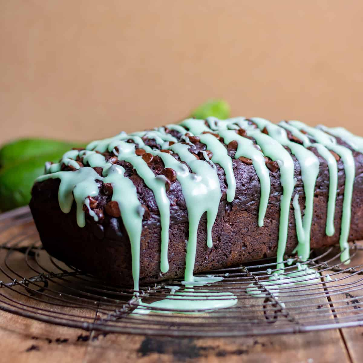 Chocolate Zucchini Bread on a wire rack with a vanilla drizzle.