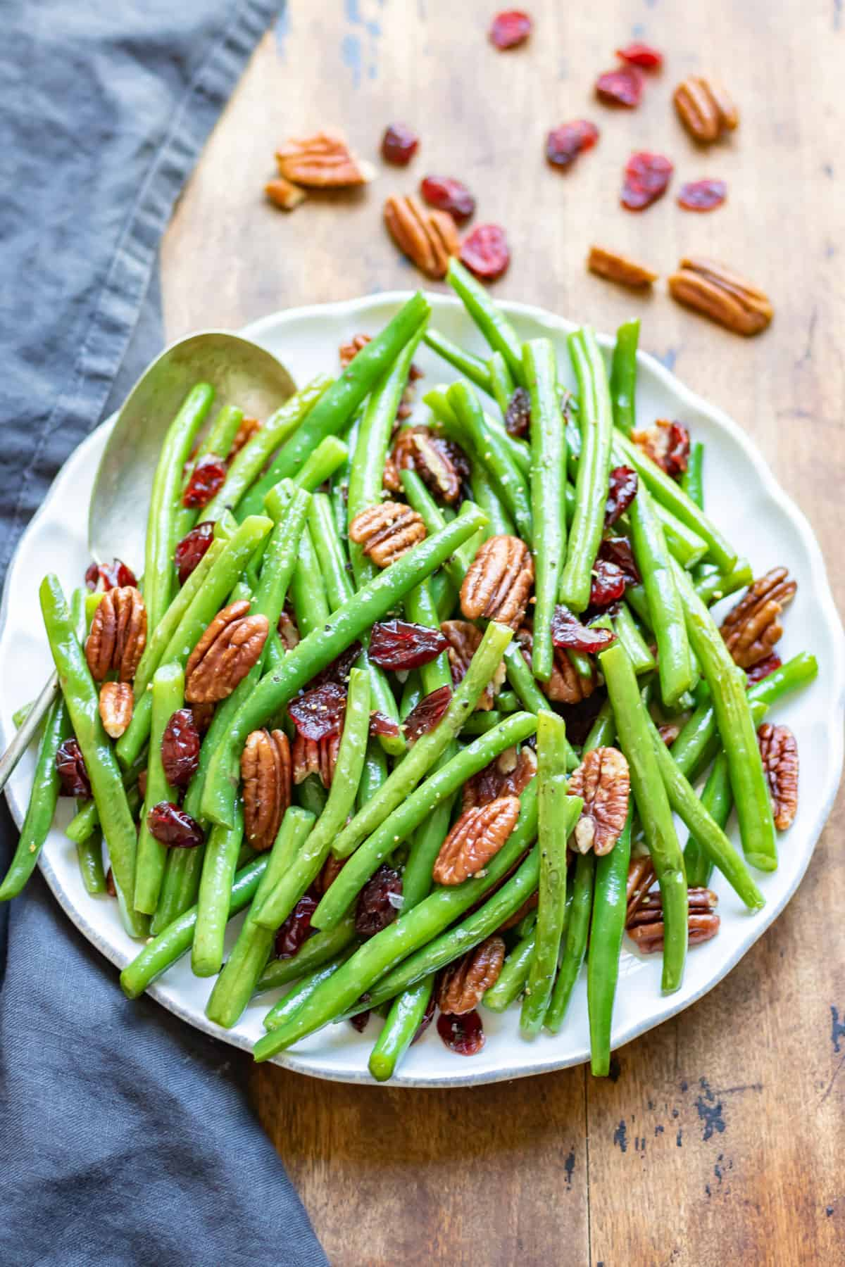 A serving dish of green beans with cranberries and pecans.