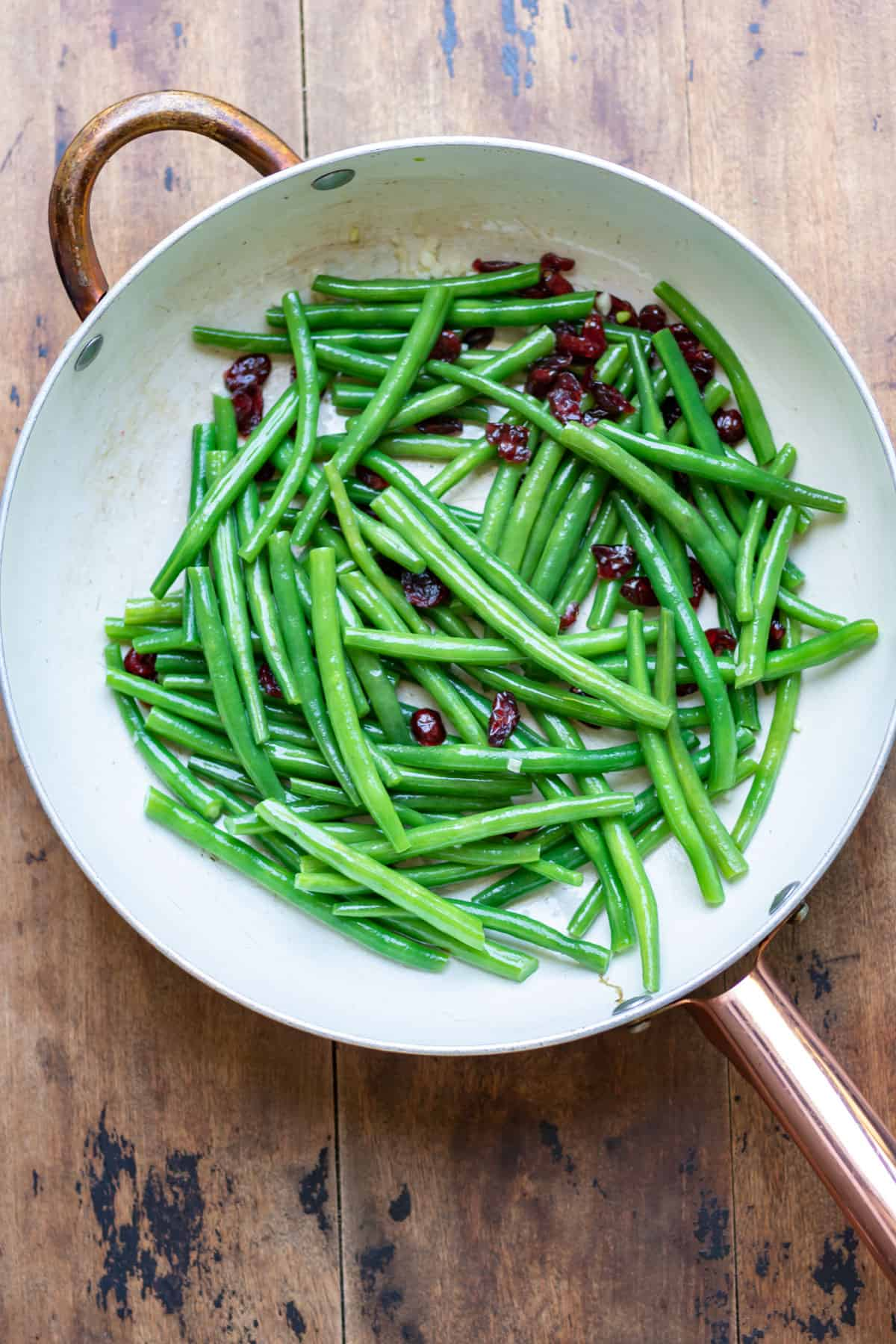 Sauteeing the cooked green beans in a pan.