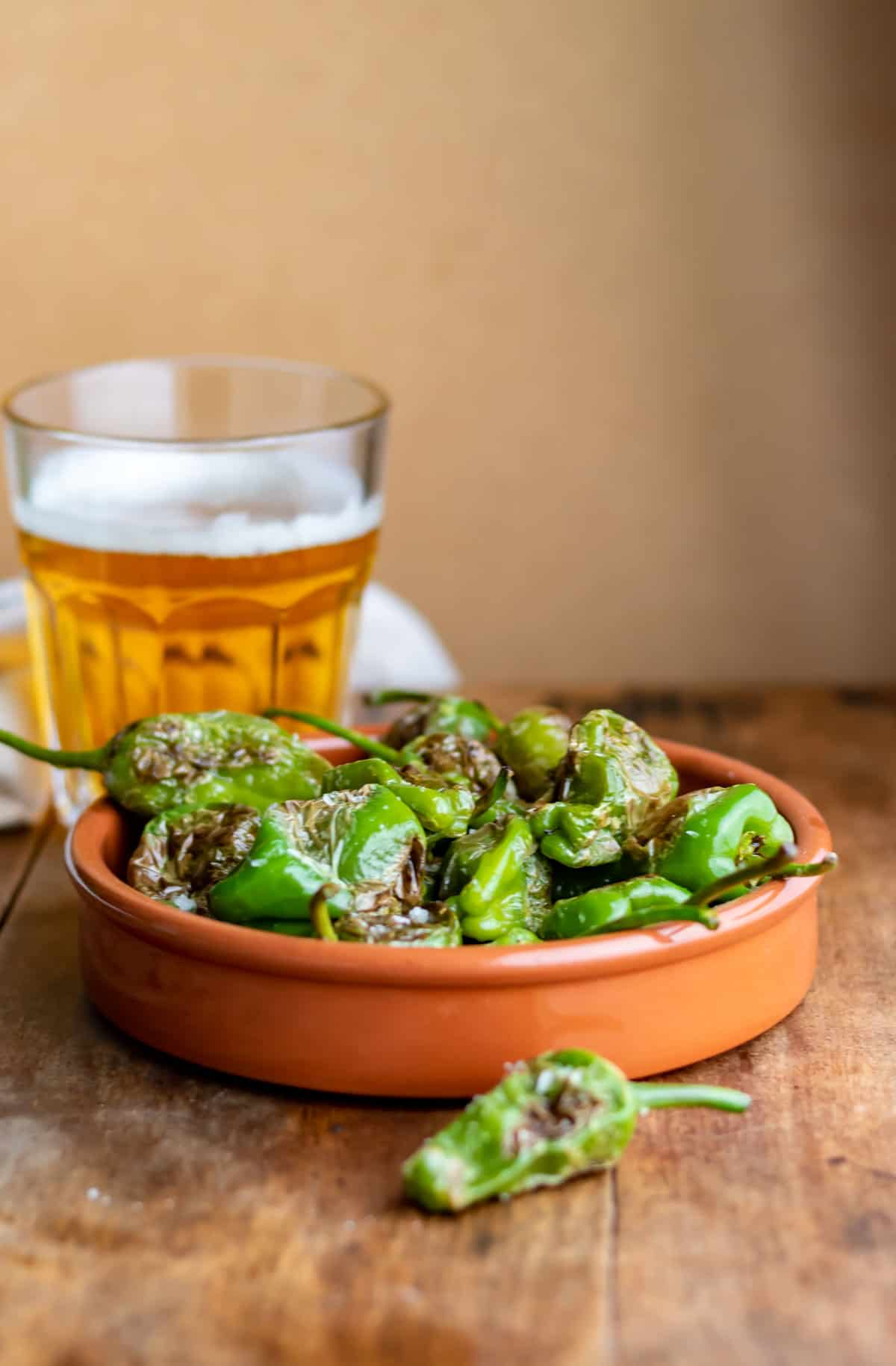 Table with a beer and dish of cooked peppers.