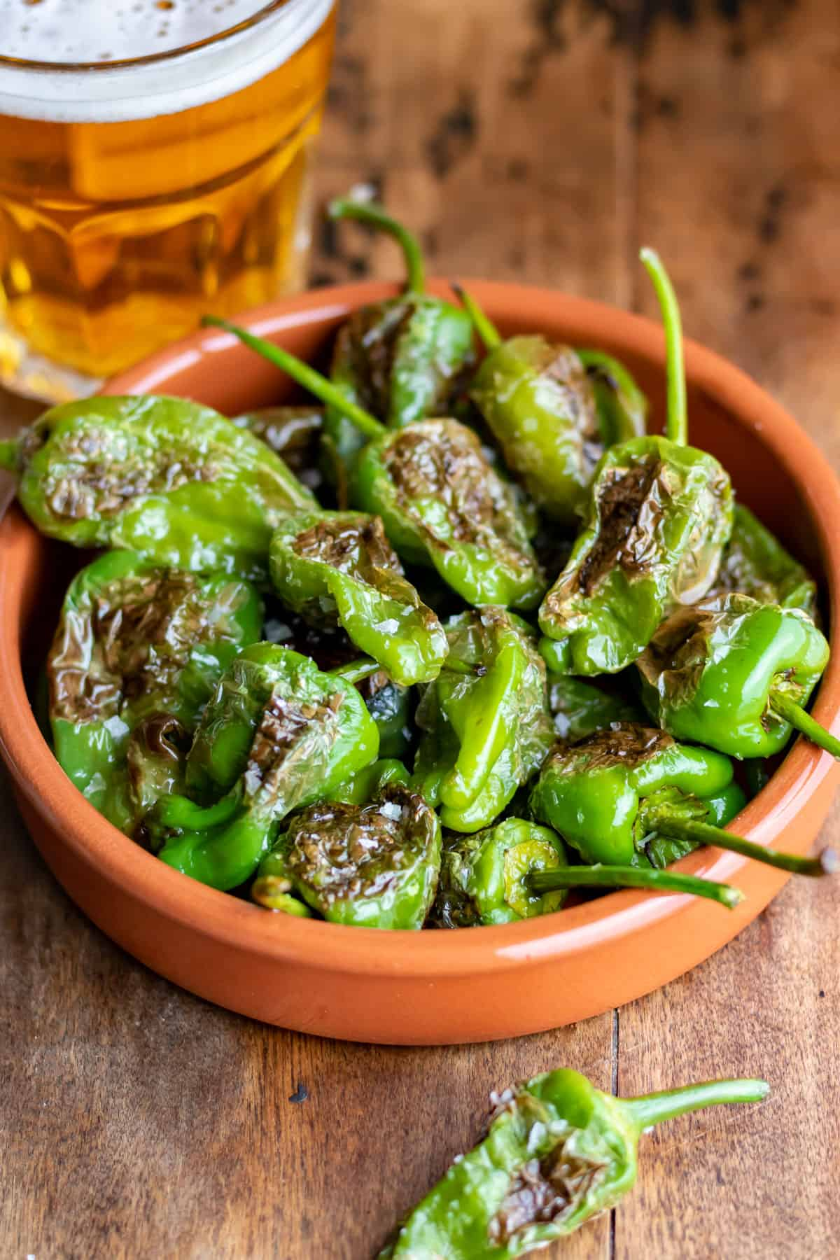 Close up of a dish of blistered padron peppers.
