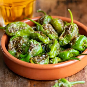 Terracotta dish of blistered padron peppers.
