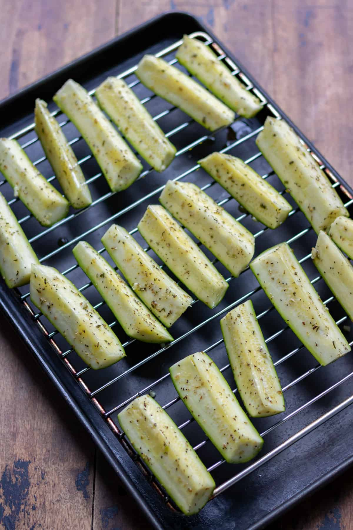 Spears of zucchini on a rack on a tray ready to roast.