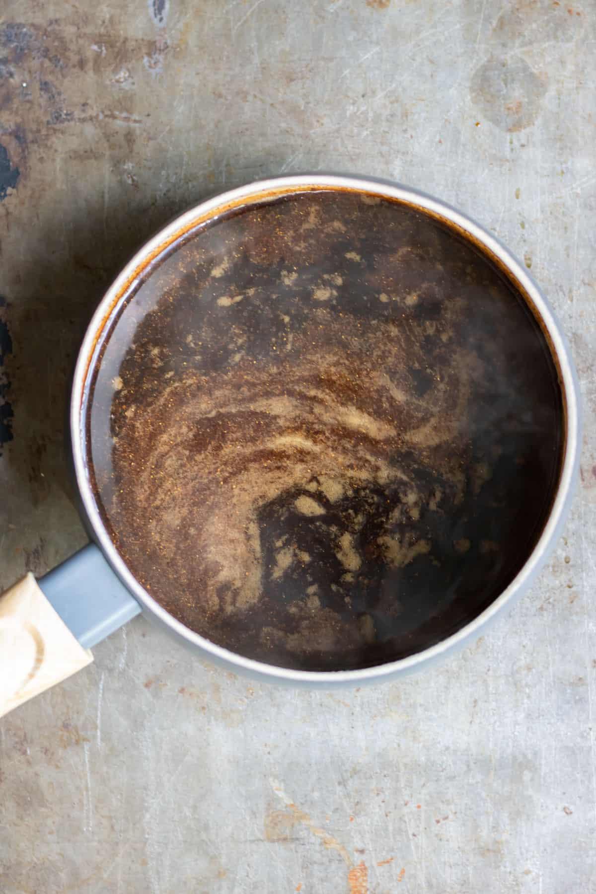 Pan of cooked vegan worcestershire sauce.