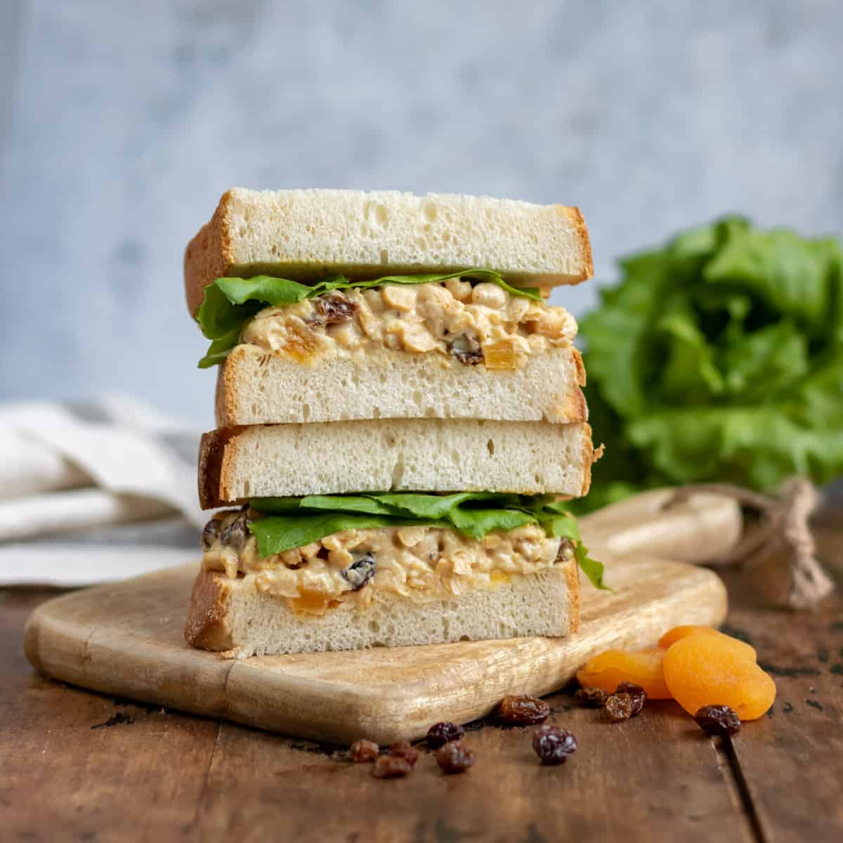 A stack of vegan chickpea sandwiches on a table.