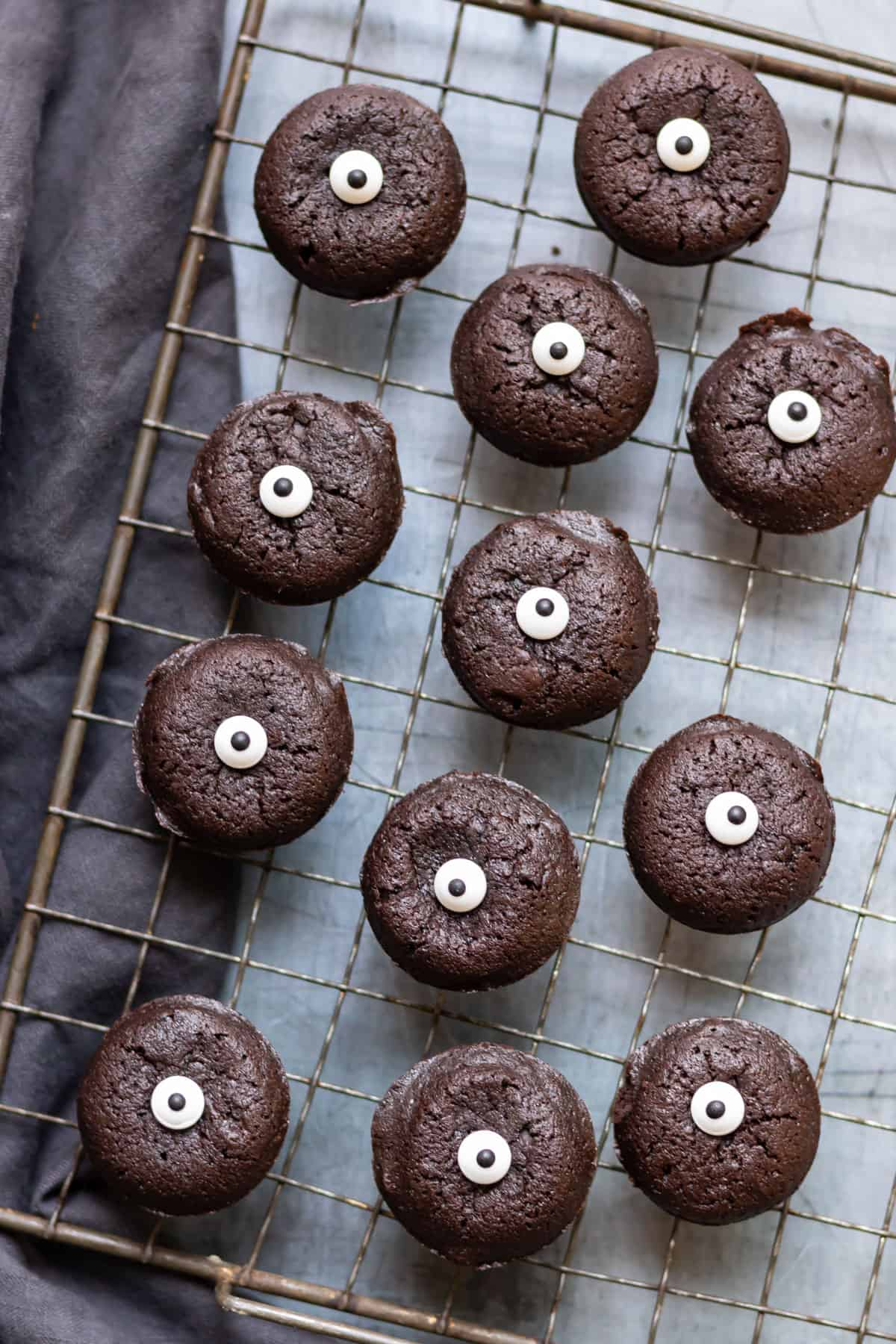 A cooling rack with brownie bites topped with candy eyeballs.