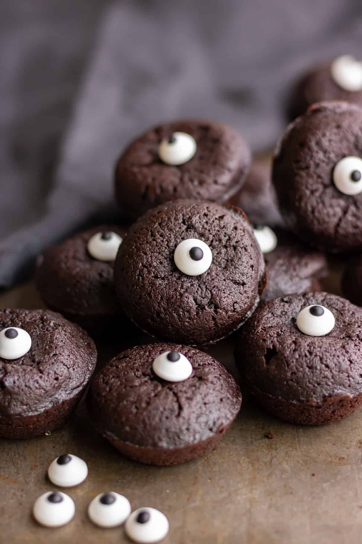 A pile of halloween brownies with candy eyes.
