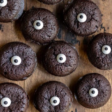 Rows of mini halloween brownie bites topped with candy eyes.