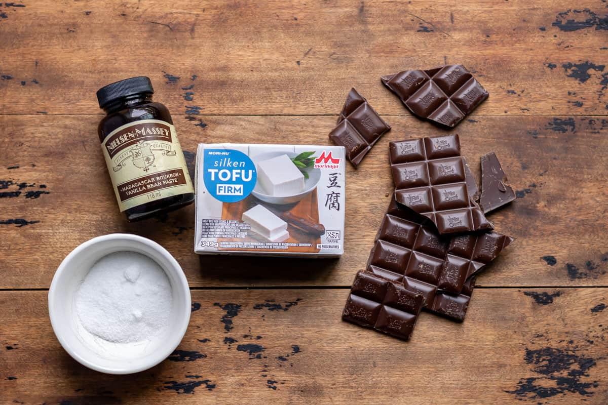 Chocolate, vanilla, silken tofu and sugar on a table.